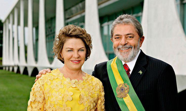 Casal, tomando mais da metade da foto. À esquerda, uma mulher de vestido amarelo, sorrindo; à direita, homem de paletó e gravata, com a faixa de presidente da república no peito, barba e cabelos brancos e a mão direita no ombro dela. Ao fundo, o Palácio do Planalto