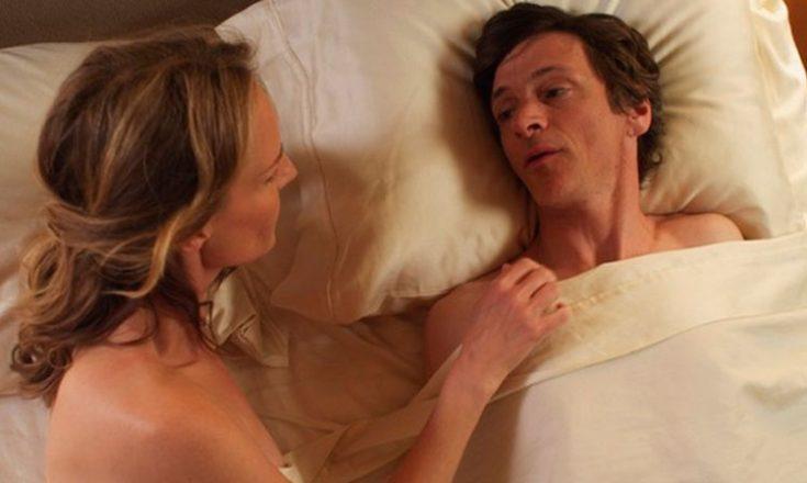 Casal na cama, sem roupa, porém cobertos por um lençol. Ela virada de lado, sobre o cotovelo esquerdo e com sua mão direita sobre o homem