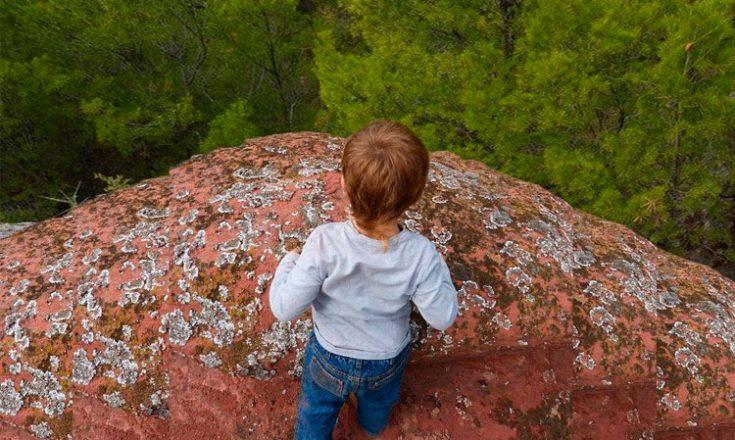 Criança de costas, caminha próximo a um precipício. No alto, árvores