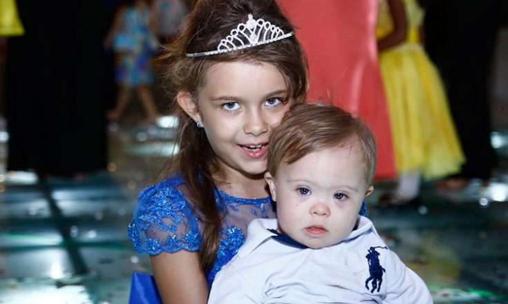 Uma garotinha de vestido azul e uma coroa branca na cabeça, abraçando um bebê de roupinha branca