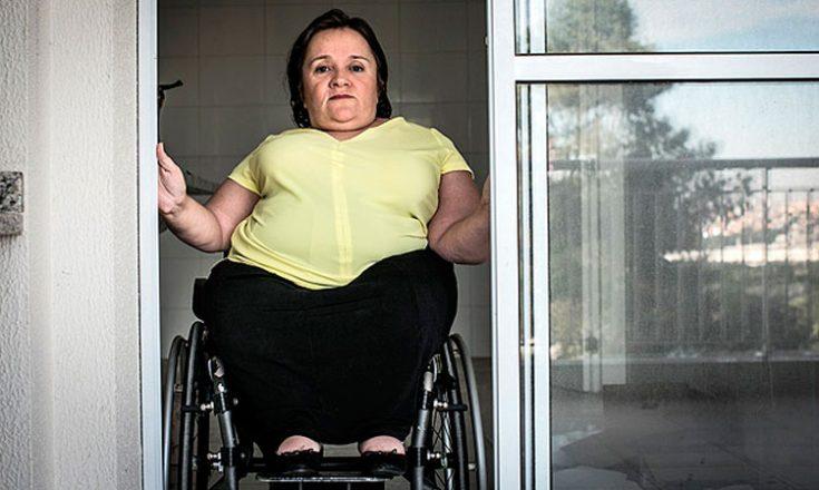 Mulher em uma cadeira de rodas, de frente, tentando passar por uma porta muito estreita