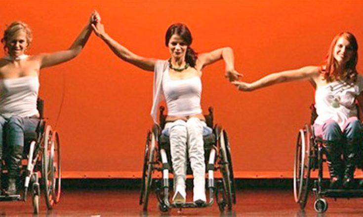 Três mulheres em cadeiras de rodas, lado a lado, de frente, se dão as mãos. Ao fundo, um painel vermelho