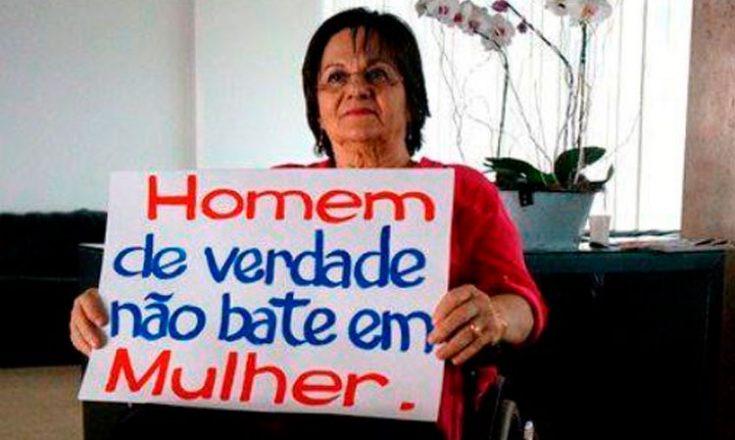 Mulher em uma cadeira de rodas, segurando um cartaz com os dizeres: homem de verdade não bate em mulher.