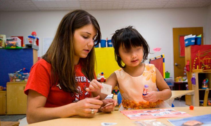 Professora e uma garotinha, em uma mesinha de escola, fazendo colagem de figurinhas em um álbum. Ao fundo, brinquedos e outras mesinhas