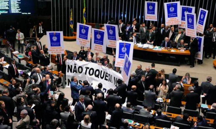 Diversos homens e mulheres, no congresso nacional, carregando placas e faixas azuis com dizeres de protesto contra a reforma trabalhista