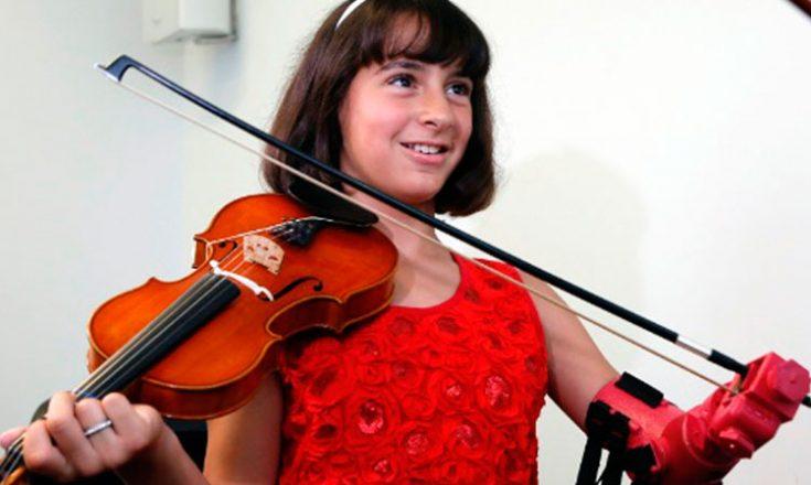 Garotinha sorrindo, em um vestido vermelho, segurando um violino e com uma prótese na mão esquerda