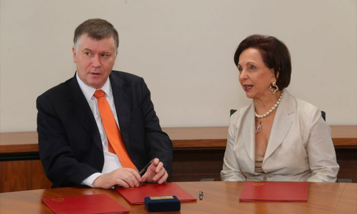 Homem de paletó preto e gravata laranja sentado em uma mesa ao lado de uma mulher com blazer cor de gelo e várias pastas vermelhas na mesa