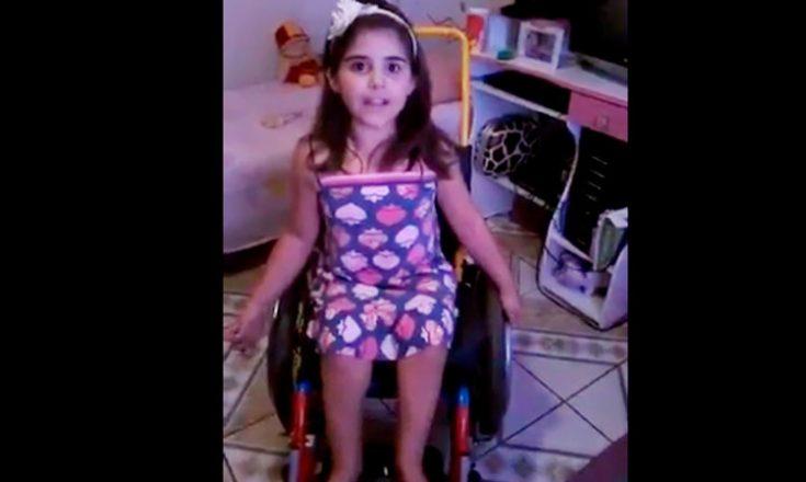 Garotinha em um vestidinho florido e com uma tiara branca, sentada em um cadeira de rodas, no seu quarto