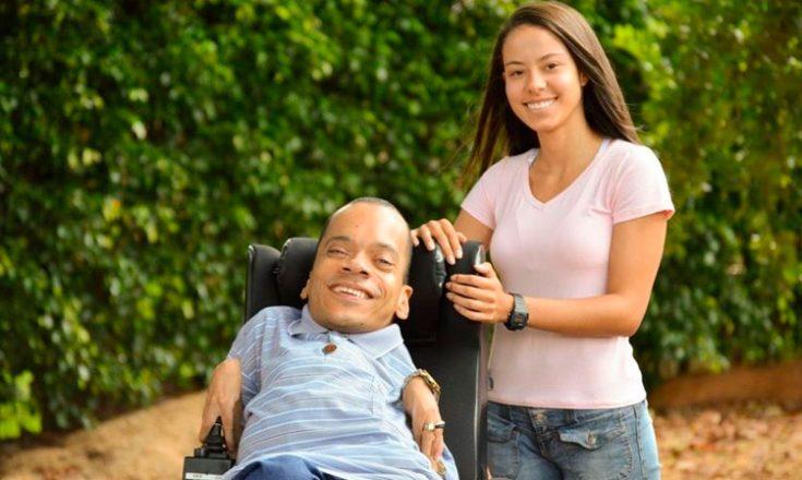 Um rapaz em uma cadeira de rodas ao lado de uma moça, ambos sorrindo, com vegetação ao fundo da foto