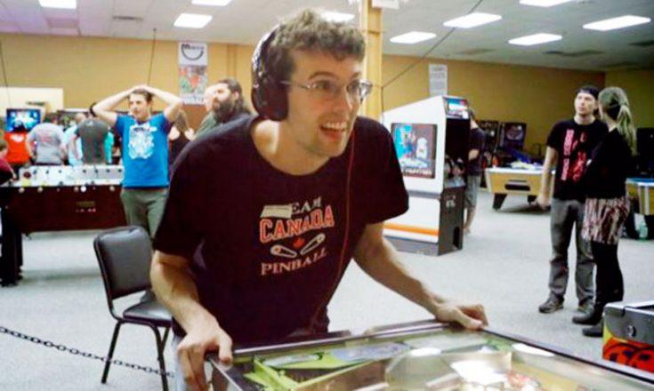 Rapaz autista, de óculos, jogando fliperama e várias pessoas assistindo
