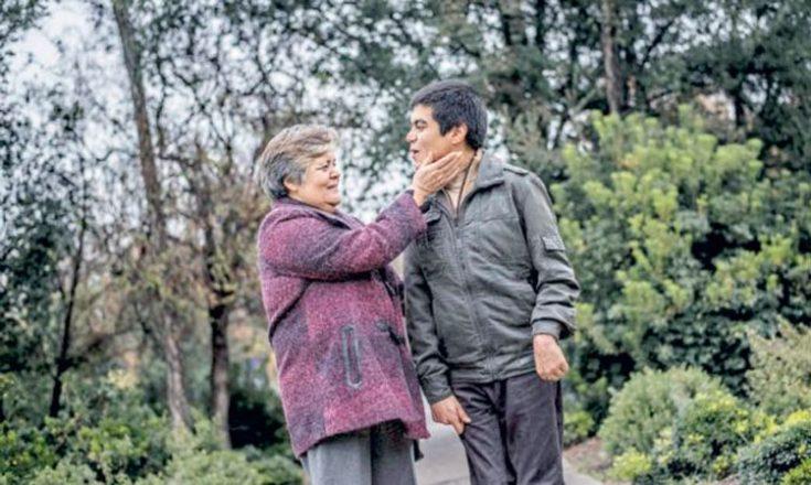 Uma senhora de cabelos brancos acaricia o rosto de um jovem, ao seu lado, seu filho, que sorri pra ela, em meio à natureza
