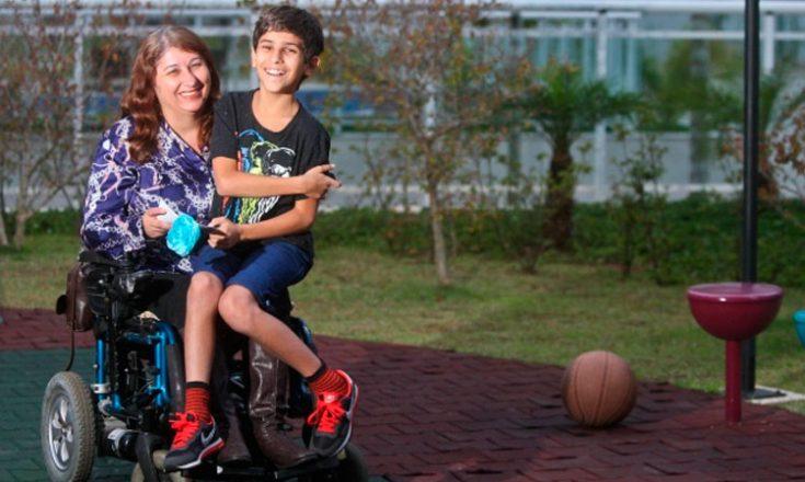 Mulher em uma cadeira de rodas, com seu filho sentado no colo. Ao fundo, árvores e uma bola de basquete ao lado deles