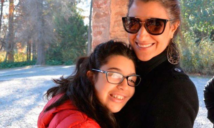Mãe e filha abraçadas e sorrindo para a câmera