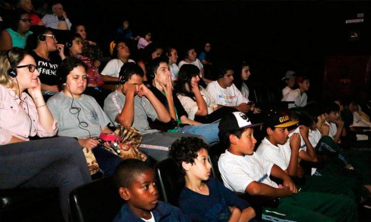 Sala de cinema com várias pessoas sentadas