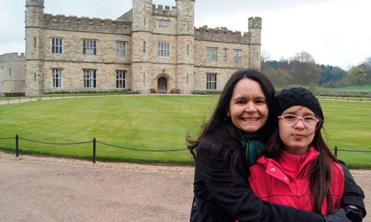 Mãe e filha posam abraçadas, em primeiro plano, e, ao fundo, um castelo medieval, uma floresta atrás dele e um grande jardim a frente