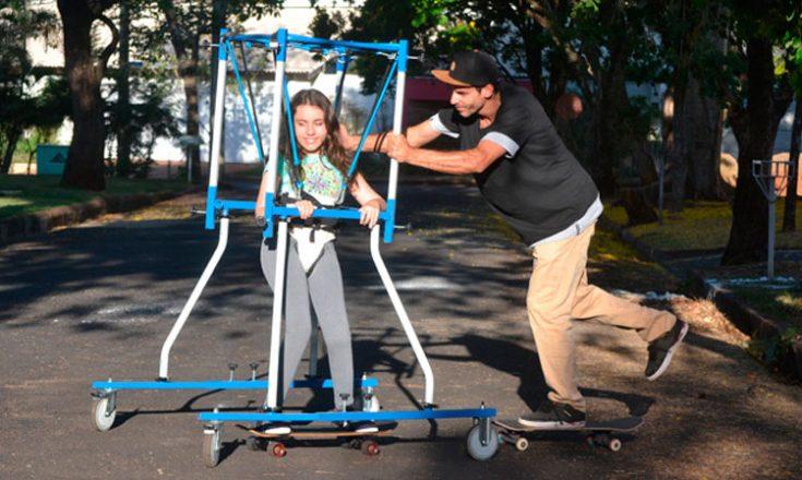Um homem, em um skate, empurra uma garotinha, também em um skate, com uma espécie de gaiola azul e branca em cima dela, presa em sua cintura por um cinto