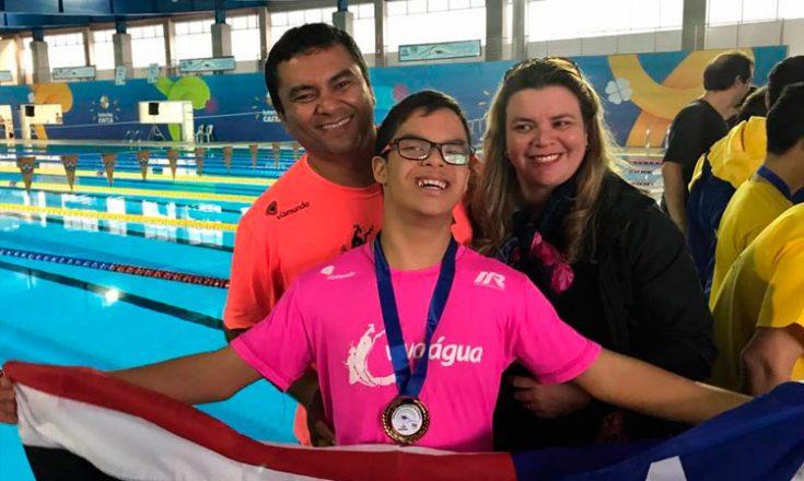 Três pessoas sorrindo, lado a lado. Um homem à esquerda, uma mulher à direita e um adolescente ao centro, com uma medalha no peito e segurando a bandeira do Estado do Maranhão