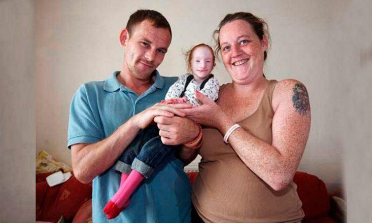 Homem e mulher, lado a lado, seguram sua filha no colo, que tem nanismo primordial