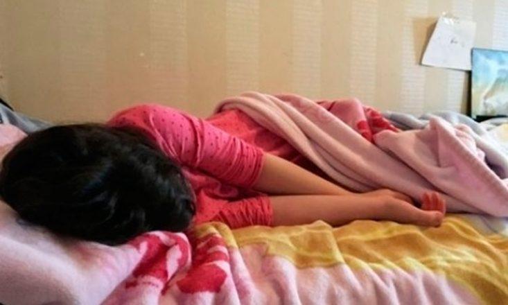 Garotinha com um pijama cor de rosa, deitada de lado em uma cama