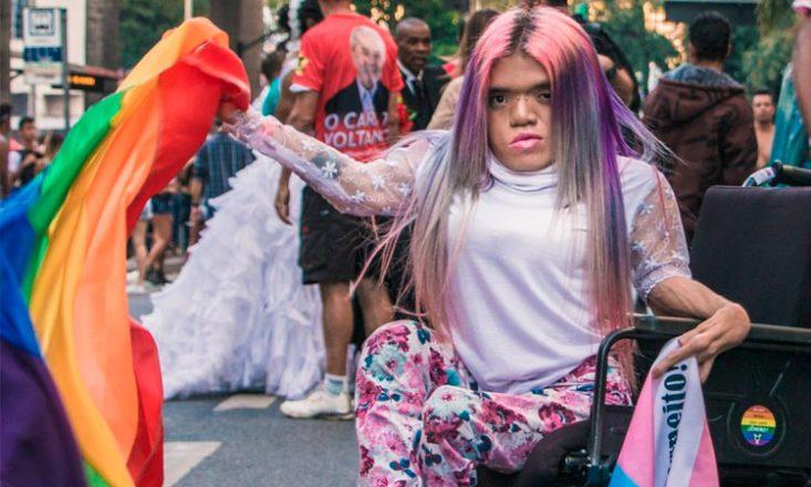 Travesti em uma cadeira de rodas, segurando uma bandeira do movimento LGBT, em meio a uma manifestação de rua
