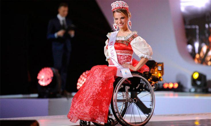 Mulher em uma cadeira de rodas, sorrindo, com as mãos na cintura, usando um vestido vermelho com mangas brancas, uma faixa no peito escrito Bielorussia e uma tiara na cabeça