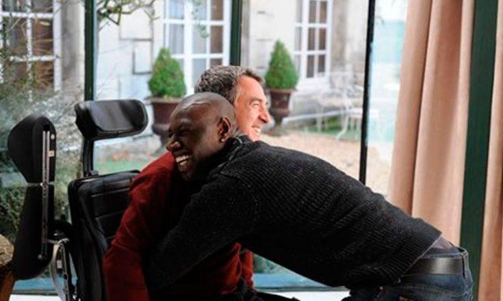 Um homem sentado em uma cadeira de rodas é abraçado efusivamente por um negro