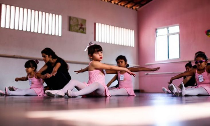 Foto horizontal de uma quadra de balé, com quatro garotinhas sentadas no chão, todas usando collant cor de rosa e realizando passos da dança, e uma professora orientando uma das meninas