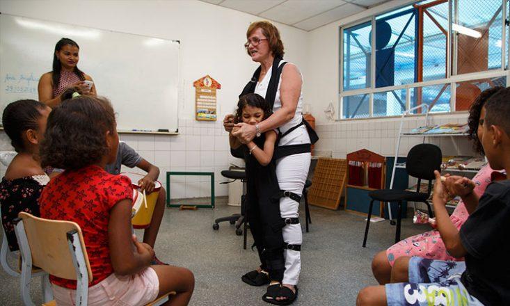 Foto horizontal em uma sala de aula. Ao centro, de pé, a professora está presa a uma aluna por um macacão. Cinco crianças e uma mulher adulta assistem