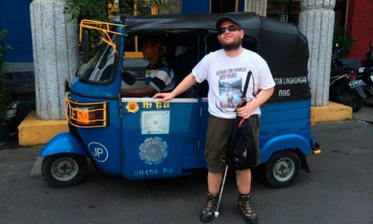 Homem em pé, com uma bengala na mão esquerda, óculos escuros, boné e bermuda, na frente de um carro pequeno azul