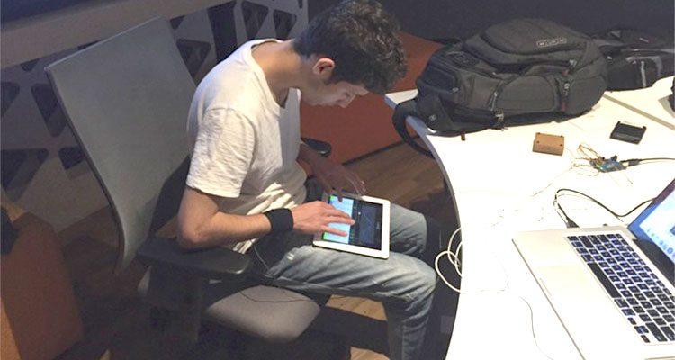 Rapaz sentado em um estúdio musical, olhando um aparelho eletrônico no colo. A sua frente, uma mesa branca com uma mochila preta no canto superior e um laptop na parte inferior