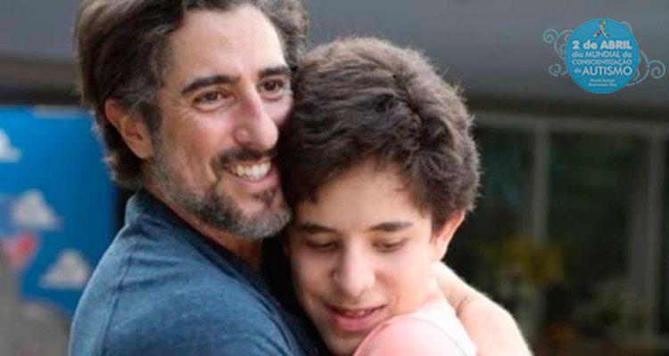 Foto horizontal, em cores, de um homem barbudo e sorridente abraçado a um jovem adolescente. No canto superior direito, a logomarca do dia mundial da conscientização do autismo, um círculo azul, com o laço colorido no alto e as palavras, em branco, 2 de abril dia mundial da conscientização do autismo