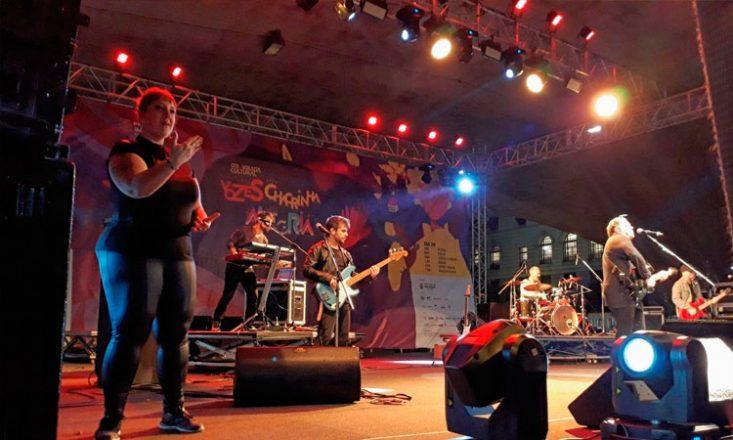 Um palco com cinco músicos à direita e uma mulher à esquerda, fazendo interpretação em Libras