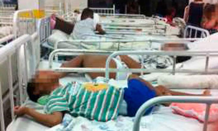 Foto horizontal de uma instituição para pessoas com deficiência, com várias camas uma ao lado da outra e internos deitados nelas