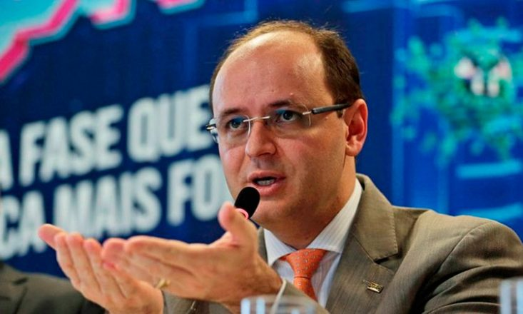 Foto de um homem de meia idade, óculos, calvo, falando ao microfone, com as mãos a frente em formato de concha