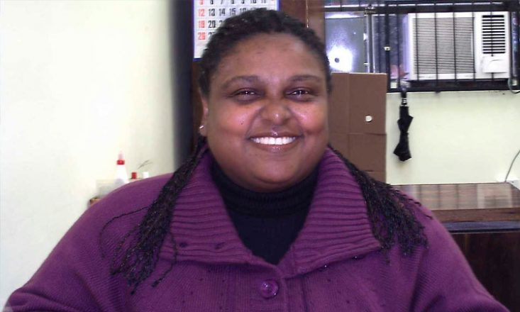 #pracegover: Foto de uma mulher negra, sorrindo, vestindo um casaco grosso lilás, em um escritório.