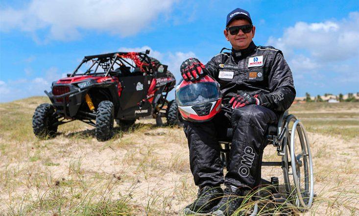 Foto horizontal no deserto de um homem, em primeiro plano, sentado em uma cadeira de rodas, com uniforme de piloto de corridas e um capacete nas mãos. Do lado esquerdo, ao fundo, um carro de rally.