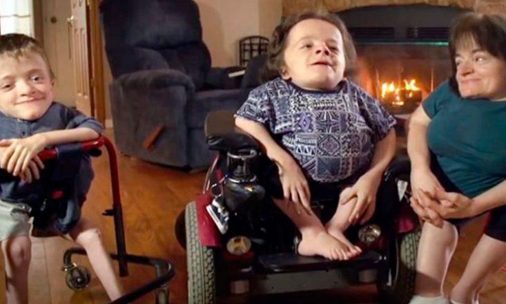 Foto horizontal de três pessoas pequenas em uma cadeira de rodas. À esquerda, um rapaz e ainda duas mulheres. Ao fundo, uma poltrona azul escura e uma lareira