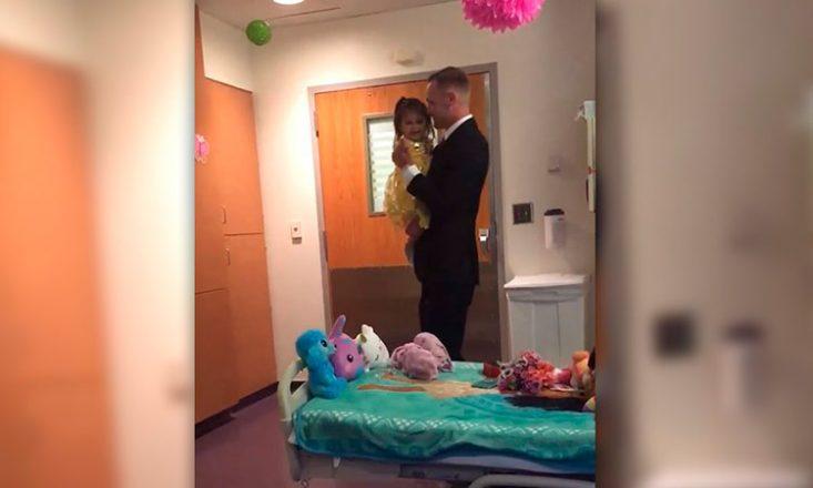 Pai e filha dançam em um quarto de hospital, com vários bichinhos de pelúcia em cima da cama. O pai veste um terno preto bastante elegante e a filha, em seu colo, usa um vestido amarelo de princesa.