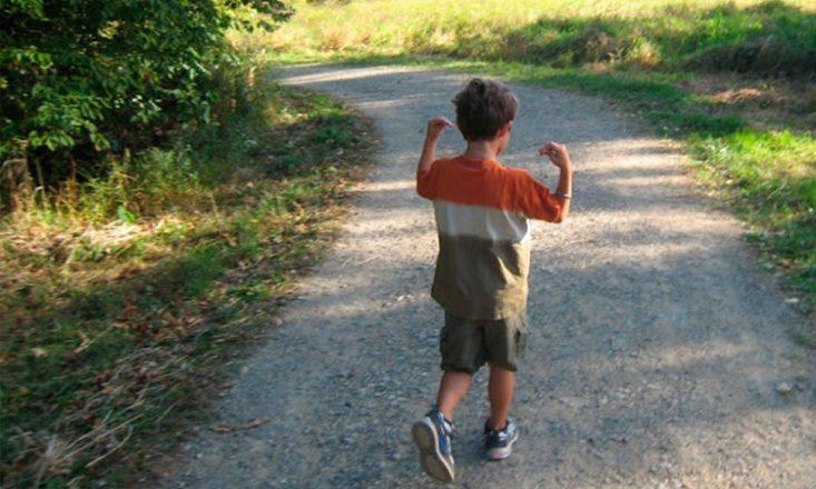 Foto horizontal de um menino autista de cerca de dez anos, de costas, vestindo uma bermuda escura, tênis azul e uma blusa tricolor em laranja, branco e marrom, caminhando por uma estrada cercada por vegetação dos lados, e realizando movimentos repetitivos com os braços.