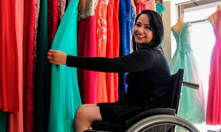Foto horizontal de Vânia Cristina sentada em uma cadeira de rodas de frente para várias roupas de cores diversas