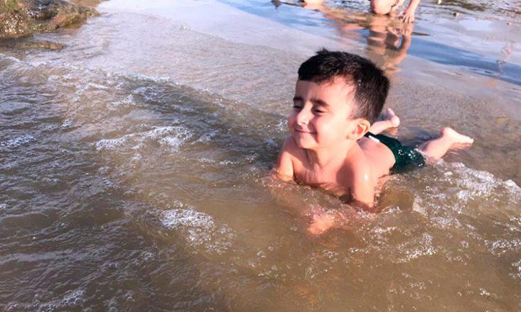 Foto horizontal de um garotinho de três anos brincando na água do mar, de bruços na areia