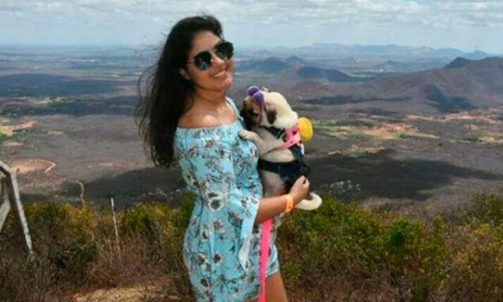 Foto horizontal, levemente borrada, de uma jovem sorrindo, de óculos escuros, segurando um cachorrinho no colo. Ao fundo, montanhas e o céu com nuvens