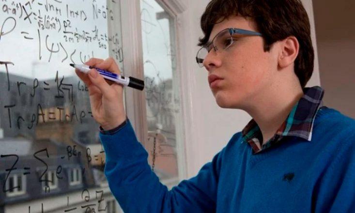 Rapaz autista escreve fórmulas de física quântica em um quadro.