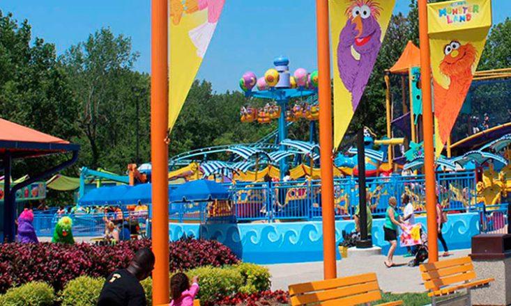 Imagem do parque de diversões Sesame Place, com postes laranjas e flâmulas de animais, em primeiro plano, e brinquedos e pessoas passeando, ao fundo.