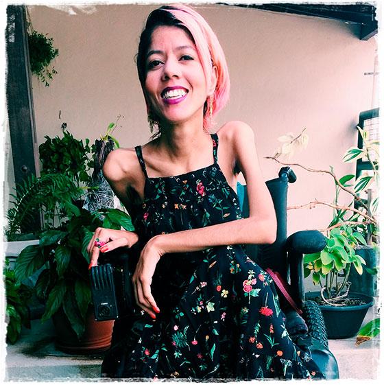 Mulher sorrindo em uma cadeira de rodas, de vestido florido, cabelos avermelhados. Atrás, vários jarros de plantas.