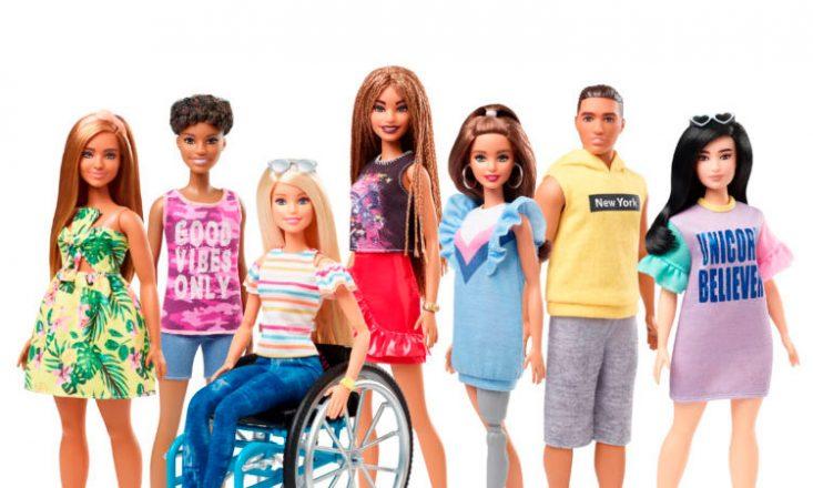 Seis bonecas Barbie dispostas lado a lado e um boneco Ken. Ao centro, uma Barbie em cadeira de rodas e outra com uma perna mecânica.