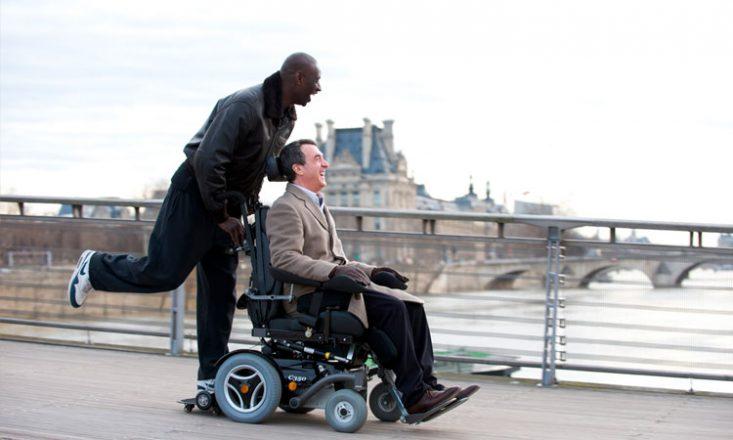 Foto horizontal de uma cena do filme Os Intocáveis, em que um homem negro empurra a cadeira de rodas do milionário tetraplégico Philippe por uma calçada. Ao fundo, um rio e um prédio lá atrás.