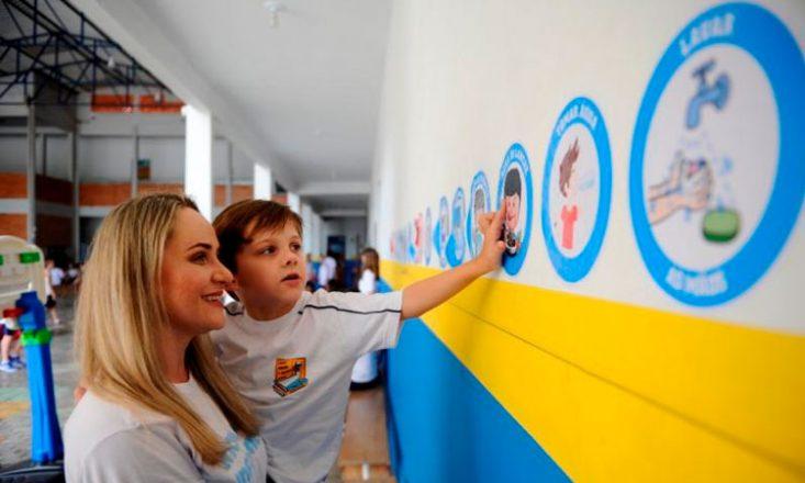 Mãe segura o filho autista no colo e ele aponta para vários adesivos pregados na parede da escola, indicando atividades rotineiras do garoto.