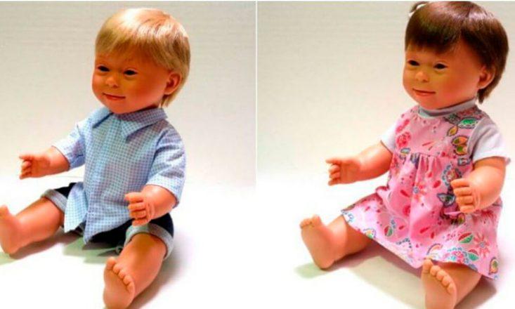 Duas bonecas lado a lado, ambas com aparência de Síndrome de Down. À esquerda, um menino loiro com uma camisa azul; à direita, uma menina morena em um vestido cor de rosa.