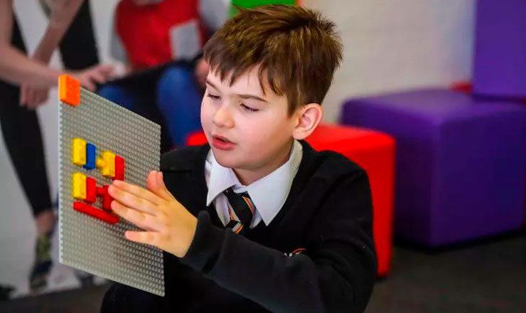 Criança cega sentada brinca com blocos de Lego construídos especialmente para pessoas com deficiência visual